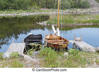 Rural wooden rowboat and sailboat at small bridges