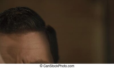 Hairdresser does hair with black comb of handsome satisfied client in professional hairdressing salon, close up