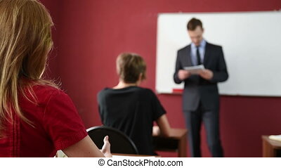 Male teacher giving a lecture at the university. students...