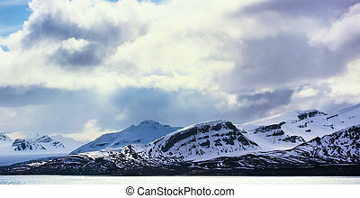 Dramatic clouds over snowy mountains in the arctic -...