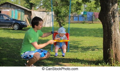 Father playing with baby boy on a swing. The garden around the house