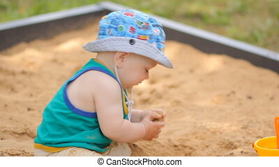Baby boy digging in the sandbox Smiles and touches the sand...