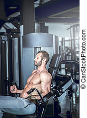 Man working out at biceps curl machine