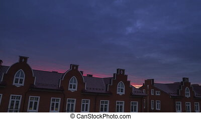 Sunset clouds over red brick town houses, timelapse video...