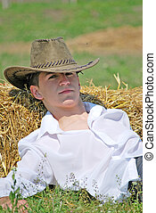 young man on hay bale - young attractive man posing on hay...
