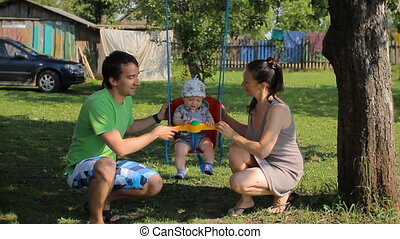Father and mother playing with baby boy on a swing. The garden around the house