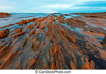 Twilight ocean coast with ribbed stratiform rock. - Twilight...