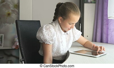 Primary schoolgirl using a digital tablet computer at home