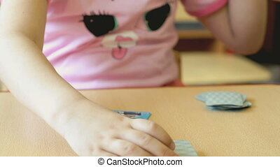 A little girl plays the playing cards at the table - The...