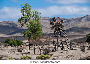 Rusty wind driven water pump in the Atacama desert, Chile. -...