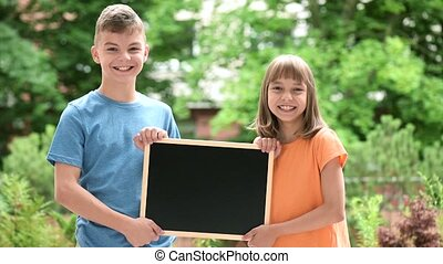 Boy and girl with blackboard - Happy boy and girl with small...