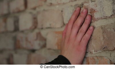 Human hand touching brick old wall in full HD