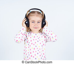 Little girl listening to music on headphones.