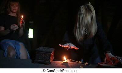 witch holding the magic ritual. old book and candle....