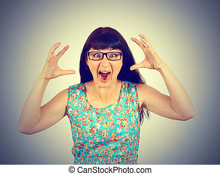 Young woman in glasses screaming in horror, grimace portrait