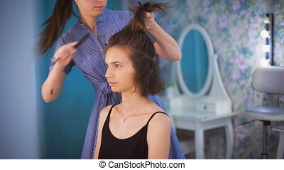 Hairdresser combing the hair of a beautiful young brunette....