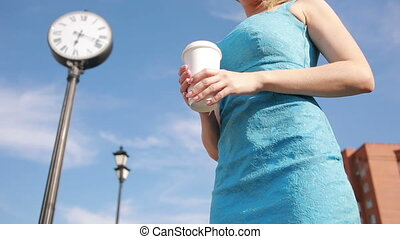 girl stands near the clock and drinking coffee waiting for...