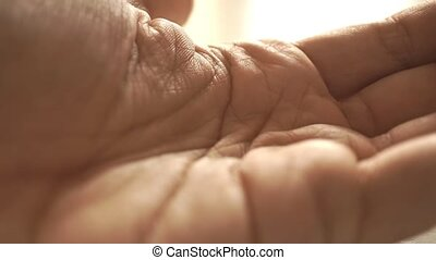 Man pouring pills from the jar on his palm macro slow motion...