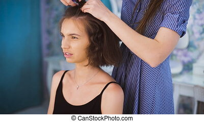 Master stylist makes styling for yong brunette To fix the...