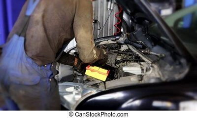 auto mechanic man changing air filter under car hood in...