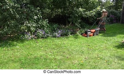 woman start lawn cutter and push near flower bed. 4K - woman...