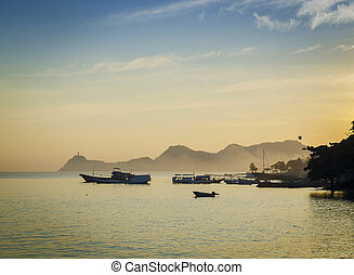 boats at harbour in dili east timor at sunset - boats at...