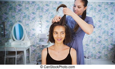 In the professional salon haircuts, the master makes hair styling for a young girl.
