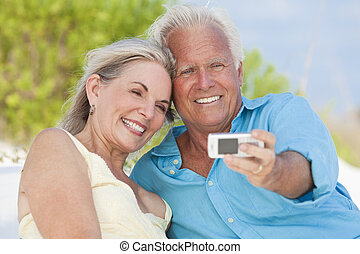 Happy Senior Couple Taking Photographs On Cell Phone At...