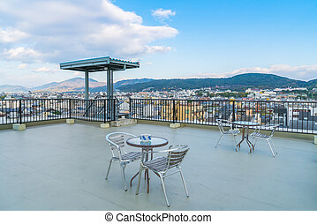 Table and chairs on roof top terrace exterior - Table and...
