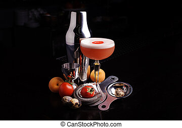 Red cocktail drink with ice. bar tools and shaker.