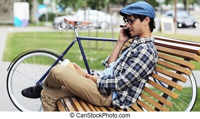 man calling by smartphone sitting on street bench - leisure,...