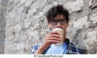 man in eyeglasses drinking coffee over street wall 21 -...