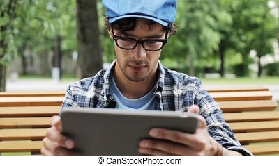 man with tablet pc sitting on city street bench 47 -...