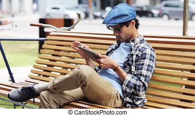 man with tablet pc sitting on city street bench 27 -...