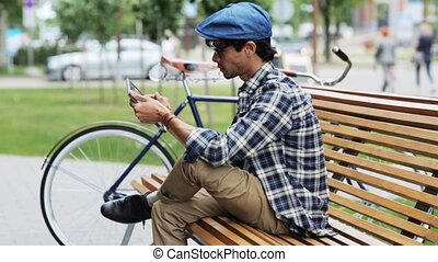 man with tablet pc sitting on city street bench - leisure,...