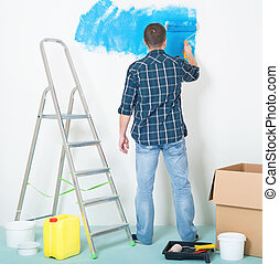 Man painting wall - Young man painting wall at home -...