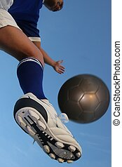 Soccer Player and Ball - Low angle of a male soccer player a...