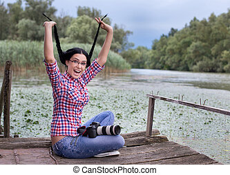 Funny girl photographer on the lake - Beautiful young woman...