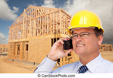Contractor in Hardhat at Construction Site Talks on His Cell...