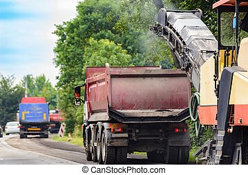 Asphalt removing machine loading powdered asphalt on the...