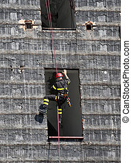 brave climber of firefighters rappelling the wall - brave...