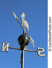 weathervane with rooster above an arrow and the four...