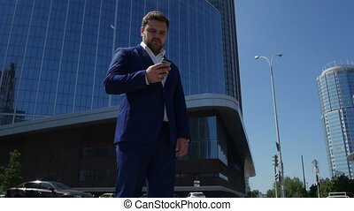 Business man in blue suit dials the phone number on the...