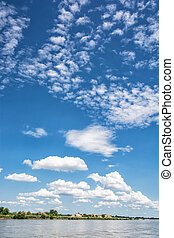 Waterfront on the Danube river and blue sky with clouds....
