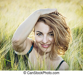 Young smiling caucasian woman posing in the wheat field,...
