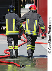 firefighters carry the hydrant and hose pipes after put off...