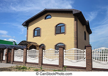 Two-storeyed yellow brick cottage with white concrete fence,...