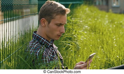 Young man sitting on the grass with smartphone - Young man...
