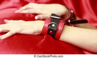 female hands in leather handcuffs. sex toys. - female hands...