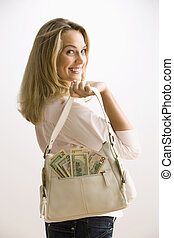 Woman Holding Cash Filled Purse - A young woman is holding a...